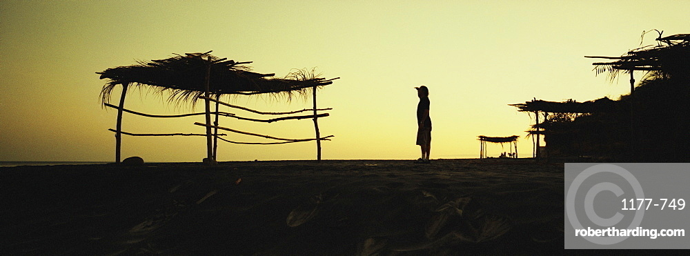 Silhouette of a palapa and a person at dusk