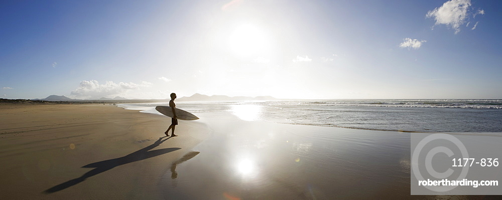 A young man standing on a beach and carrying a surfboard