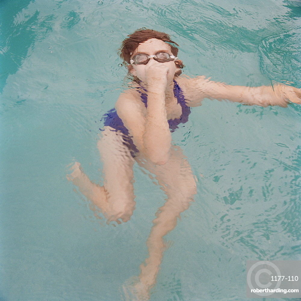 A girl holding nose underwater