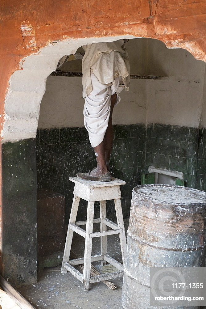 Low section of house painter standing on table