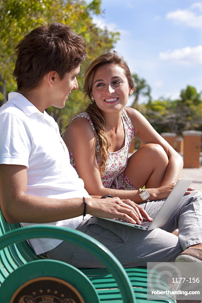 A young couple sitting on a park bench using a laptop