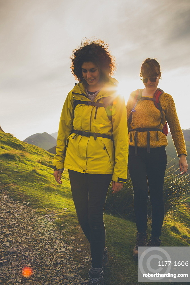Female friends walking on mountain against sky during sunset