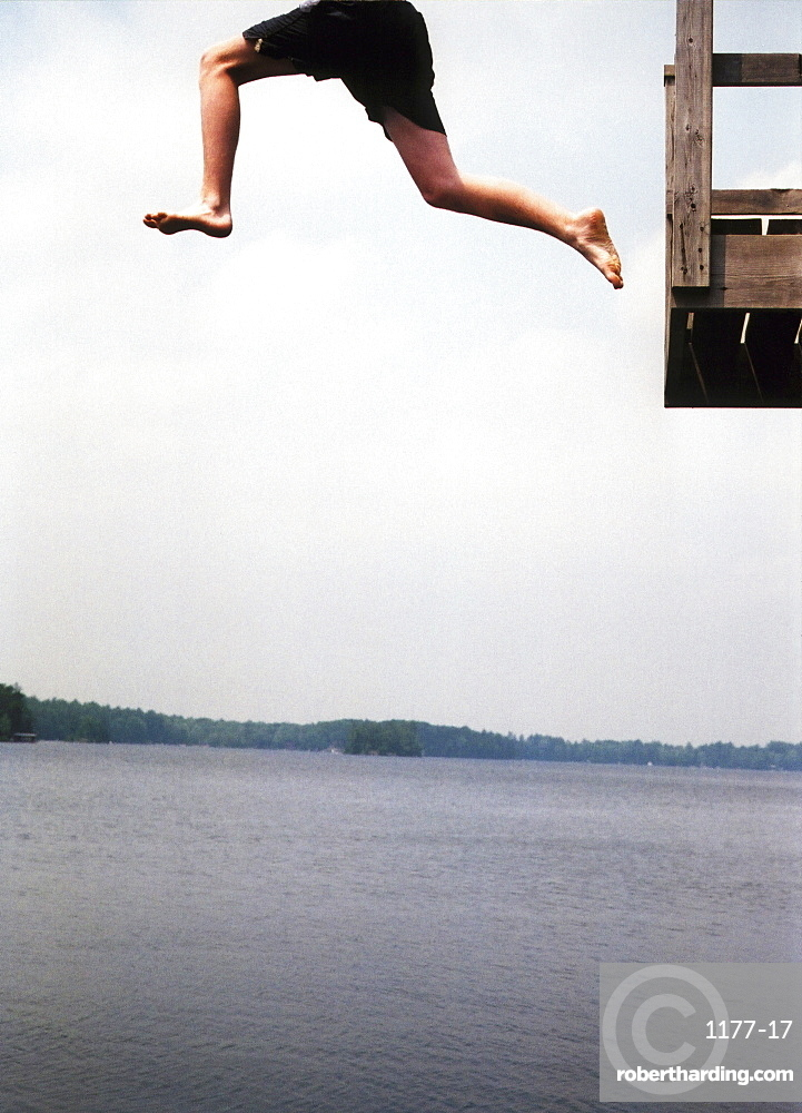 A person jumping off a platform into a lake