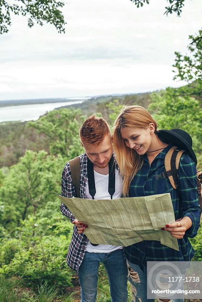 Smiling couple reading map while hiking in forest