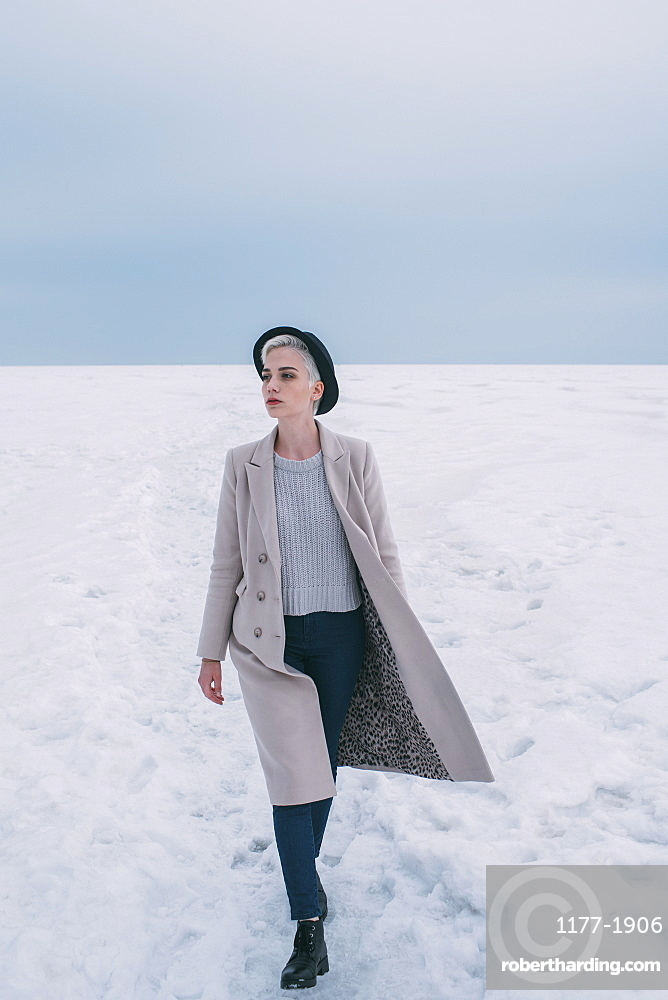 Woman in coat and hat walking in snow covered landscape