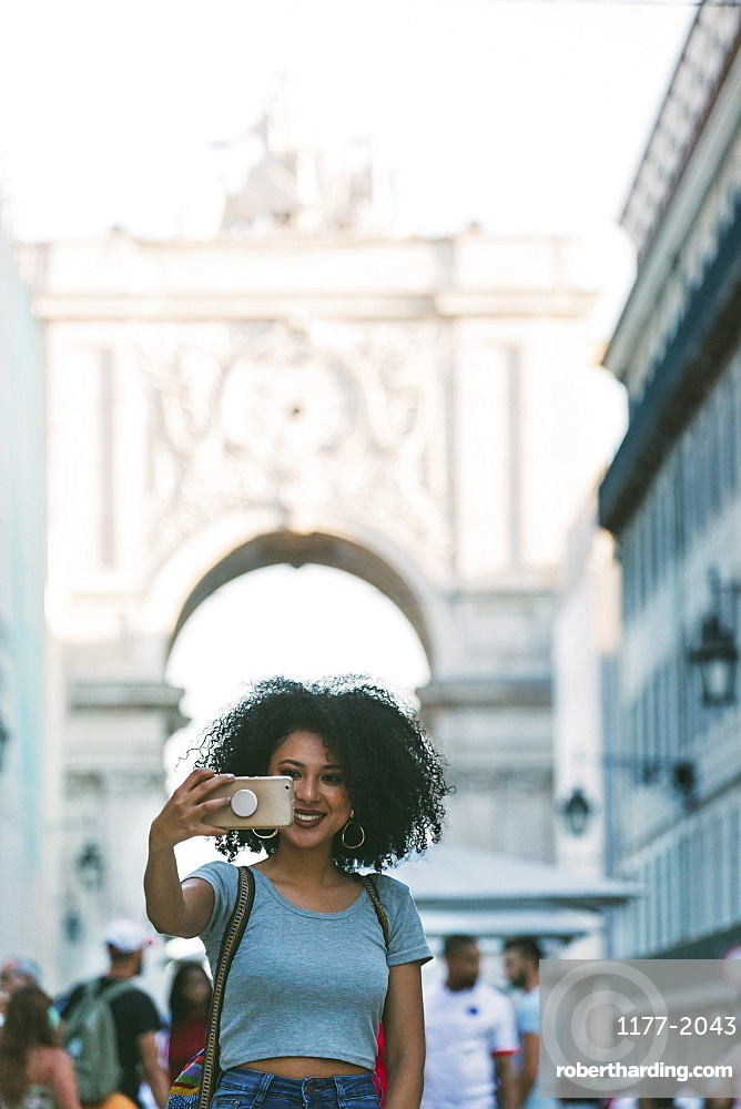 Young woman with smart phone taking selfie with Rua Augusta Arch, Lisbon, Portugal