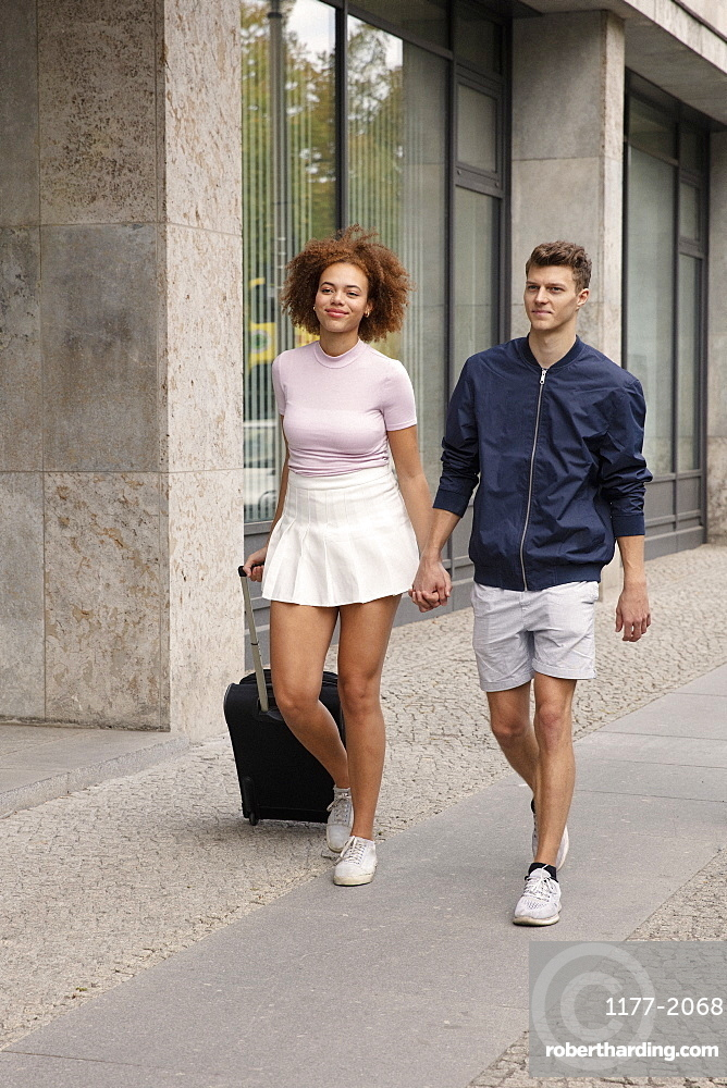 Young couple with suitcase walking on urban sidewalk