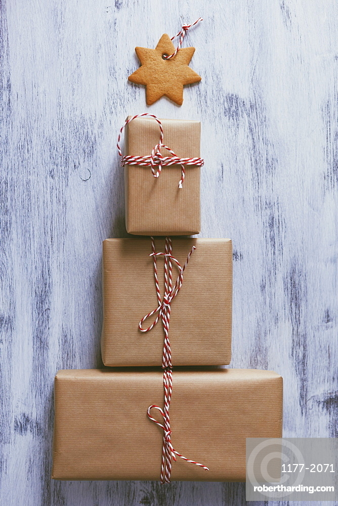 Wrapped Christmas presents arranged in the shape of a tree with a cookie star atop