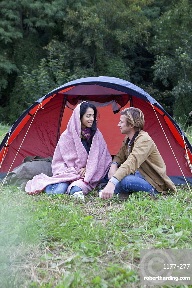 Young couple sitting near dome tent