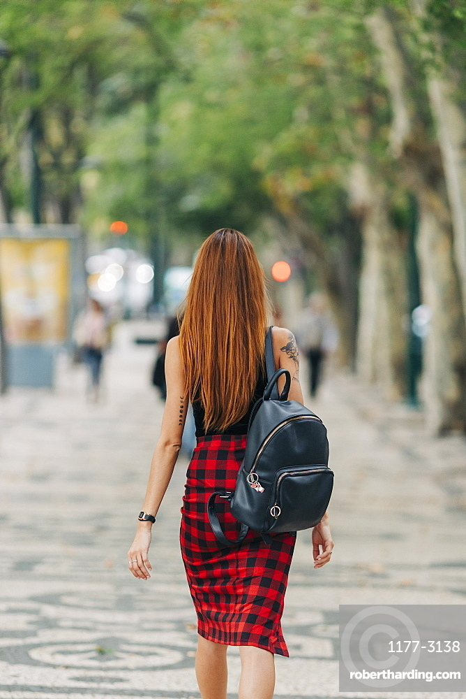 Young woman with backpack walking in urban park