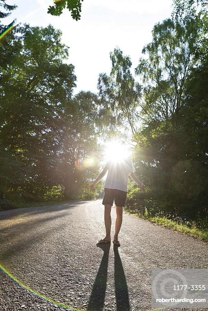 Man standing below trees on sunny road