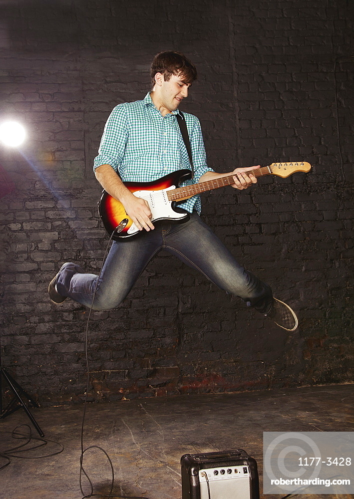 Teenage boy playing electric guitar and jumping above amplifier