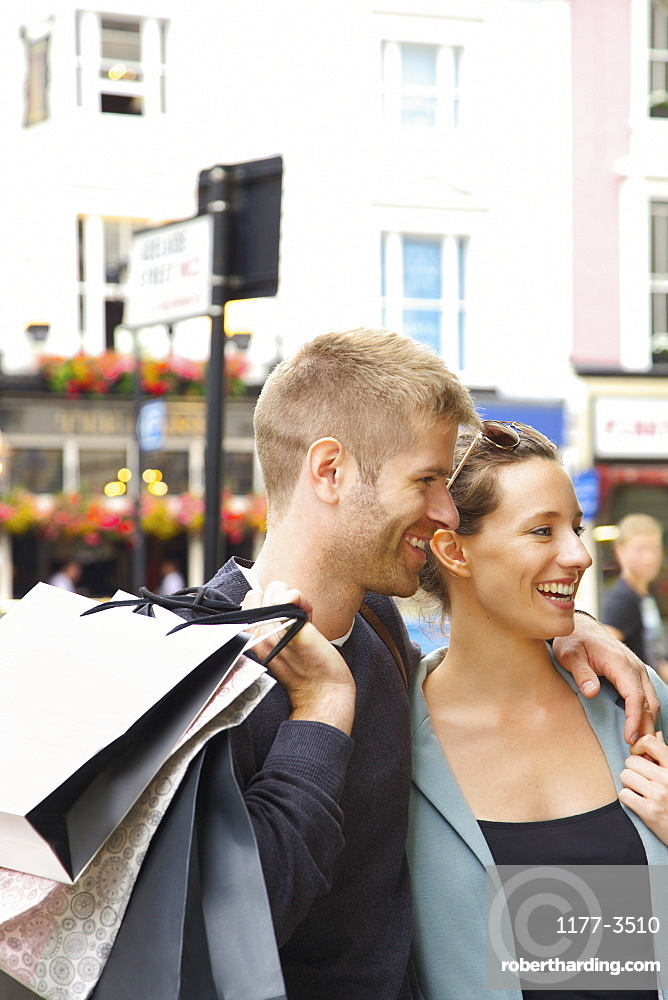 Happy couple shopping in city