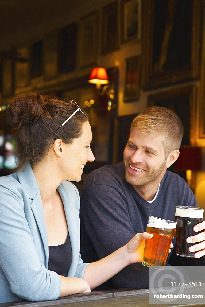 Happy couple drinking beer in pub