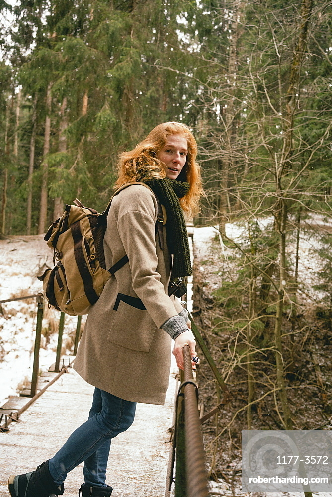 Portrait redhead woman with backpack on footbridge in snowy woods