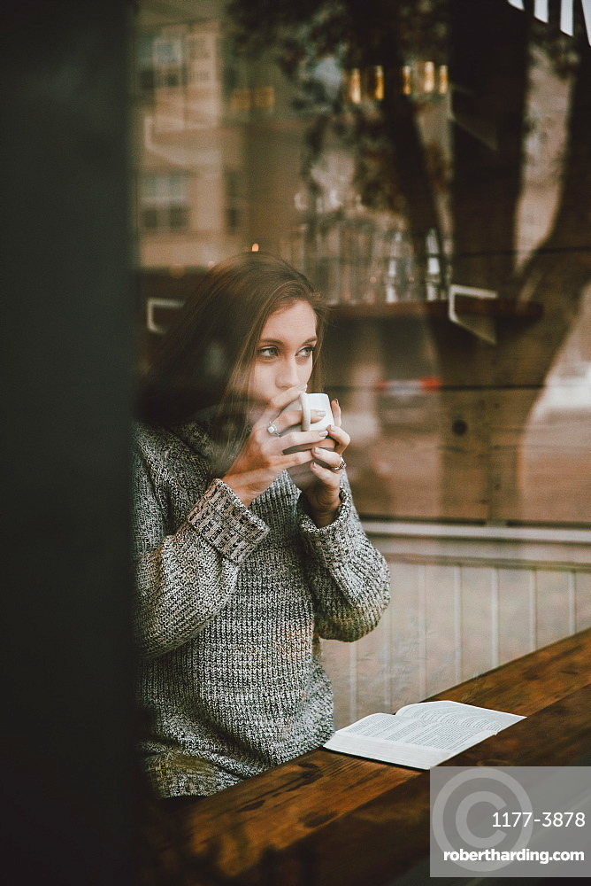 Young woman drinking coffee and reading book at cafe window
