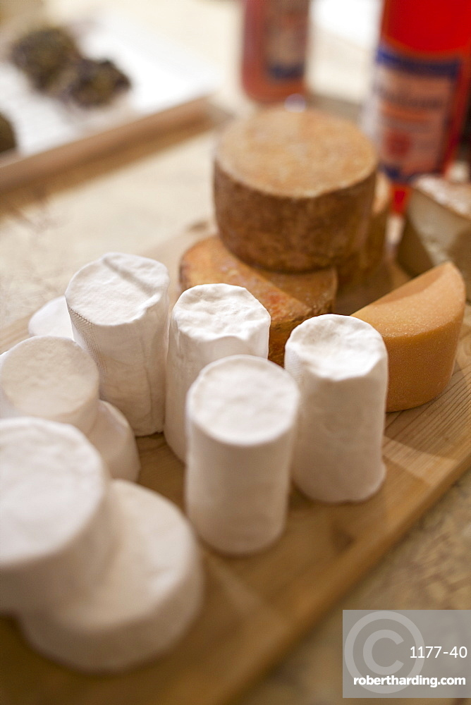 Several kinds of wrapped cheeses on wooden chopping board on table