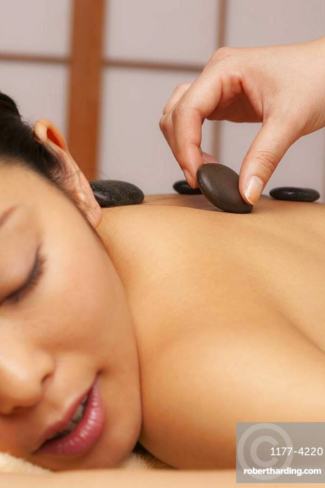 Close up young woman receiving hot stone massage