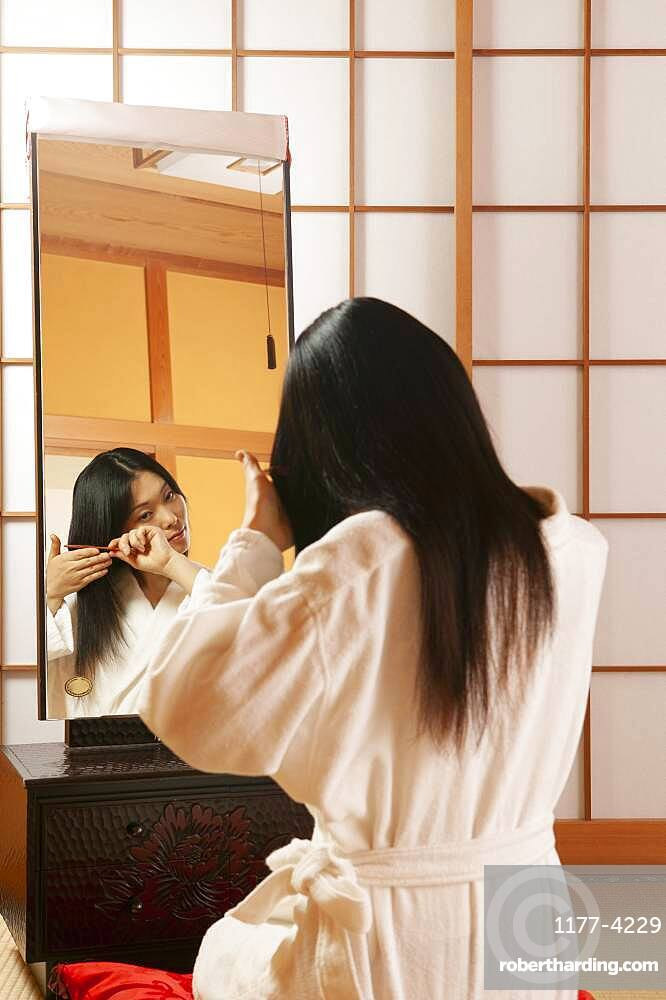 Young woman in bathrobe combing hair at mirror in spa