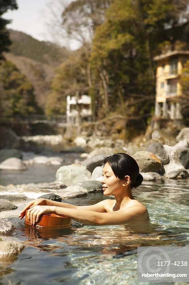 Young woman with bucket in sunny pool at Onsen