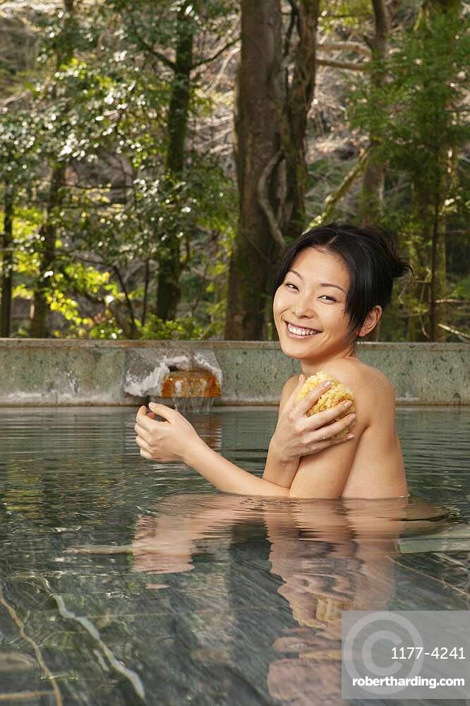 Portrait happy young woman with loofah in pool at Onsen