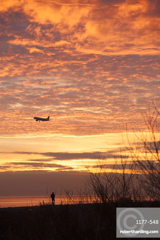 Airplane against cloudy sky during sunset