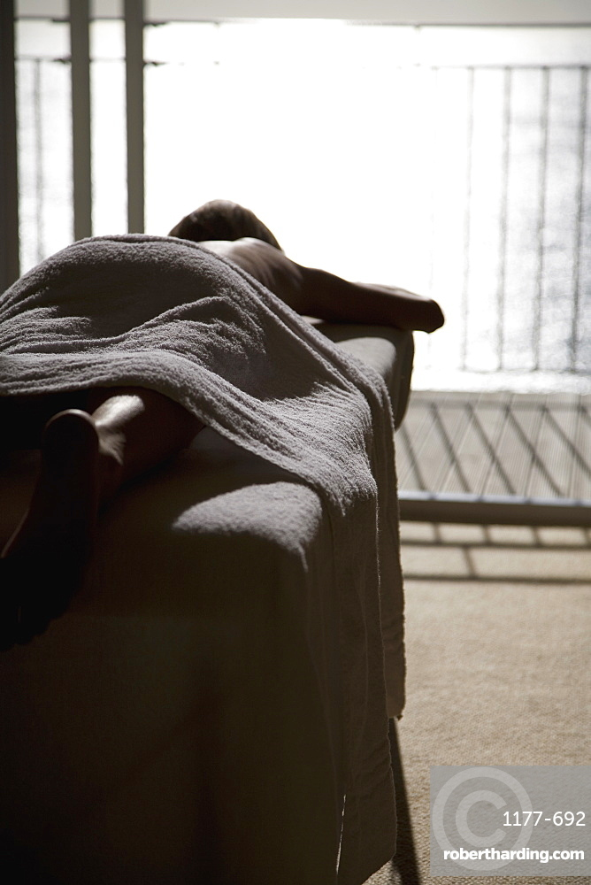 A woman lying down on a massage table