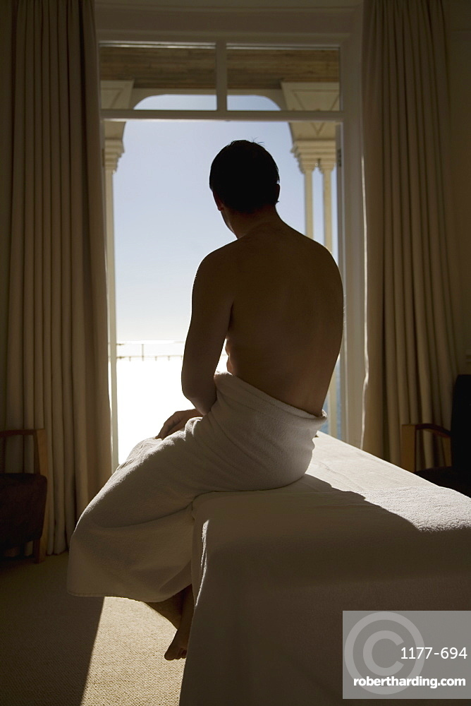 A man wrapped in a towel and sitting at the edge of a massage table
