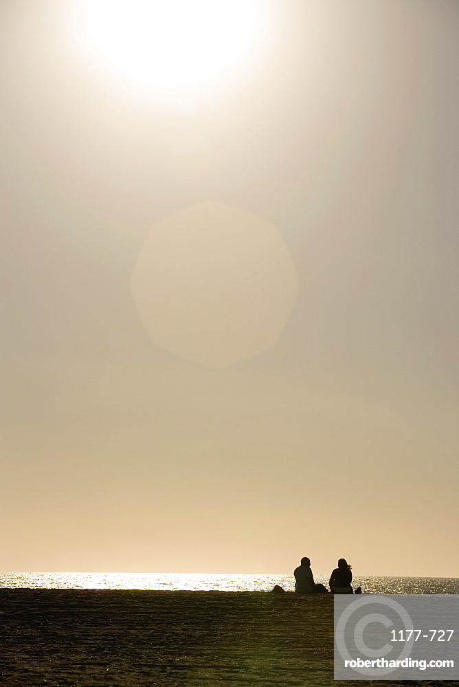 A couple sitting on the beach at sunset