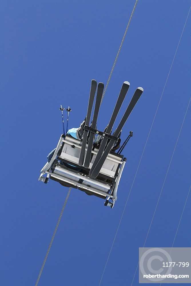 Two skiers sitting on a ski lift