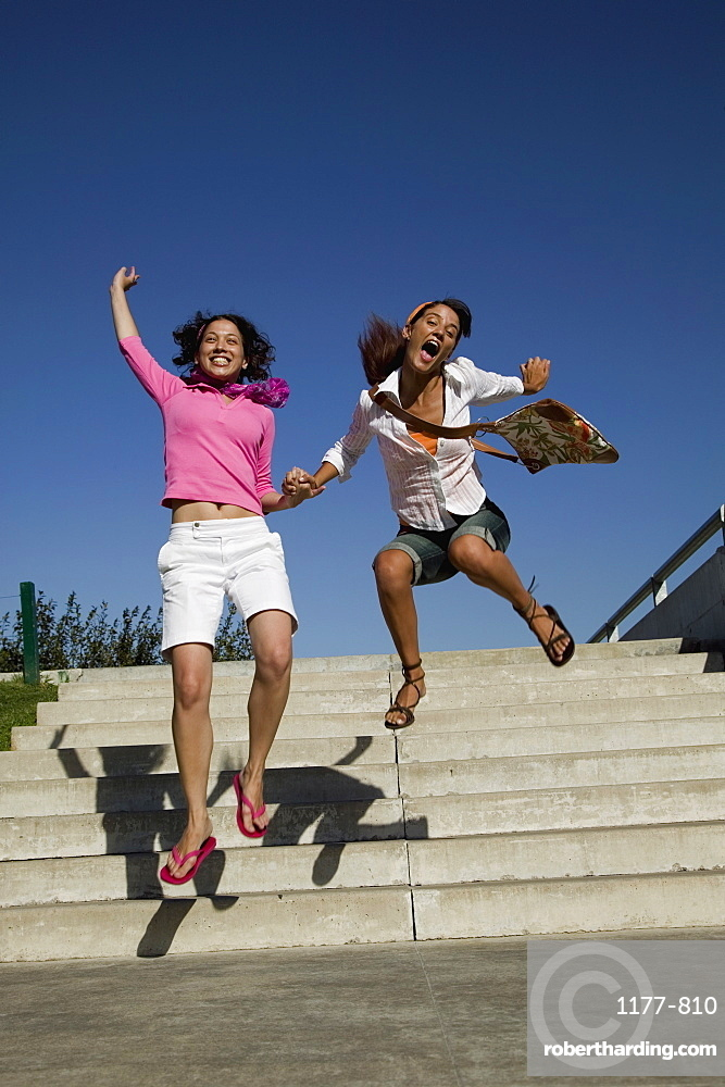 Two young women leaping in excitement
