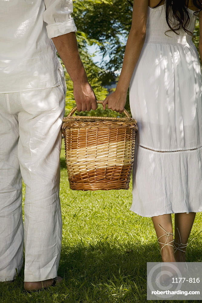 A young couple holding a basket together