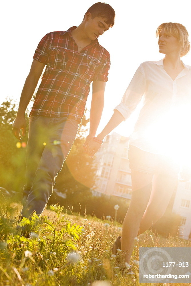 A young couple holding hands walking through a park, front view