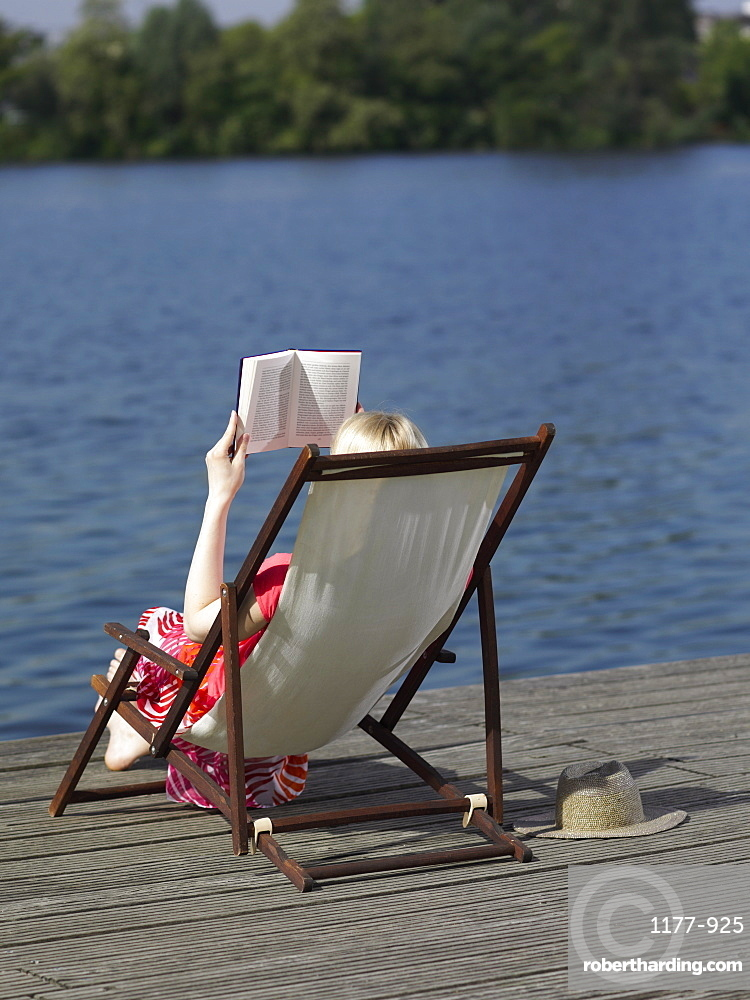 A woman reading in a reclining beach chair on a dock
