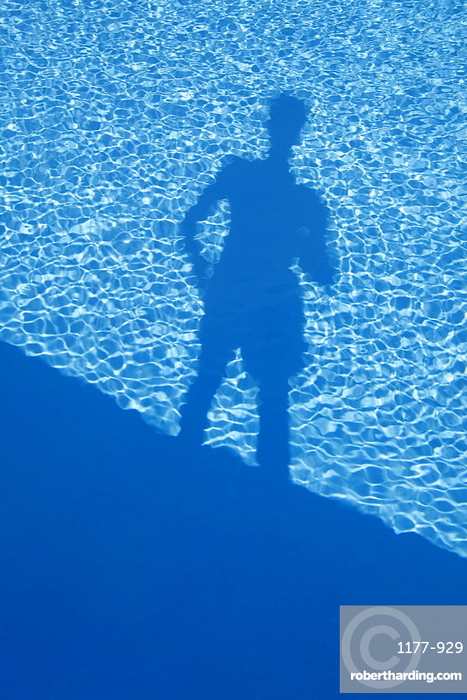 Shadow of a man standing at the edge of a swimming pool