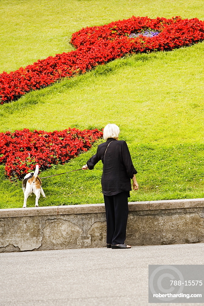 Rear view of a woman with her dog in a garden, Scalinata Delle Caravelle, Genoa, Liguria, Italy
