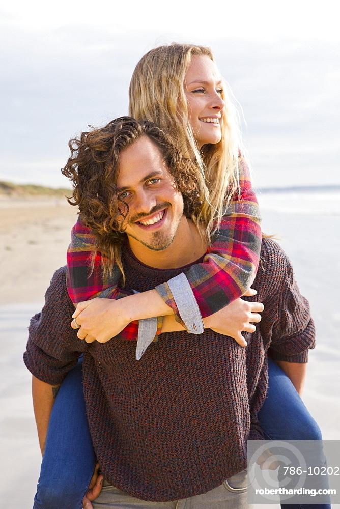 Portrait smiling couple piggybacking on beach