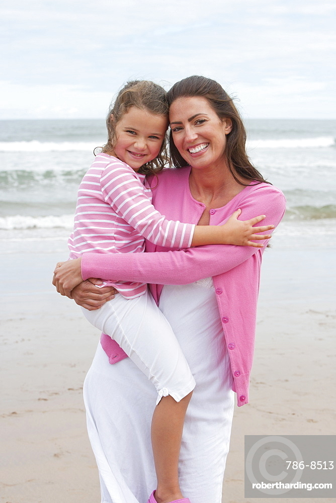 Mother And Daughter Walking Along Summer Beach