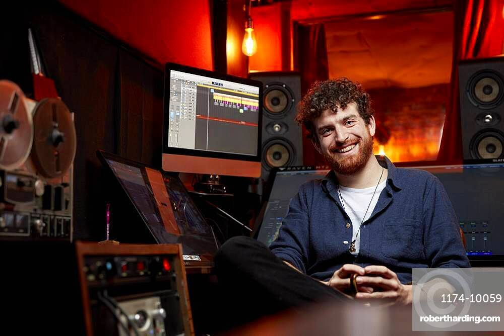 Portrait of man smiling, sitting in music studio holding cup of coffee