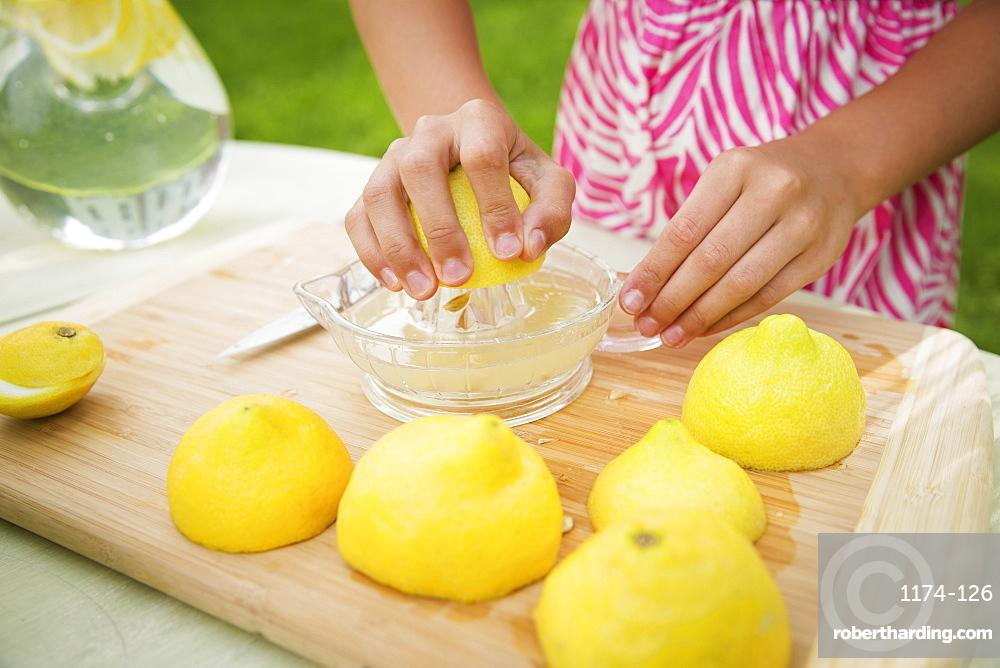 A summer family gathering at a farm. A girl slicing and juicing lemons to make lemonade.