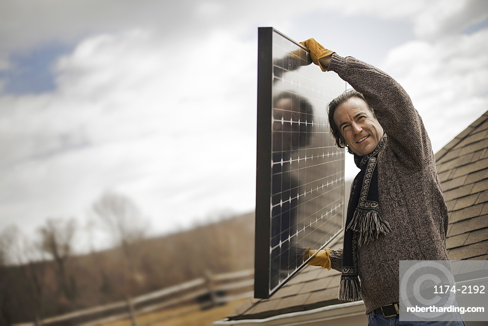 A man carrying a large solar panel across a farmyard, Cold Spring, New York, USA