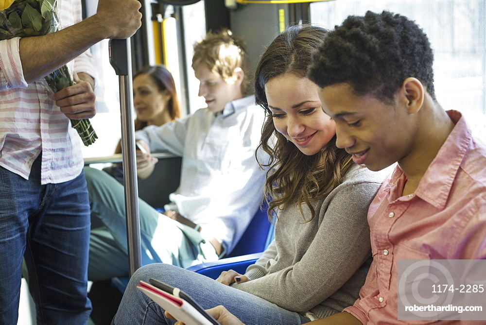 Urban Lifestyle. A group of people, men and women on a city bus, in New York city. A couple side by side looking at a digital tablet, New York city, USA