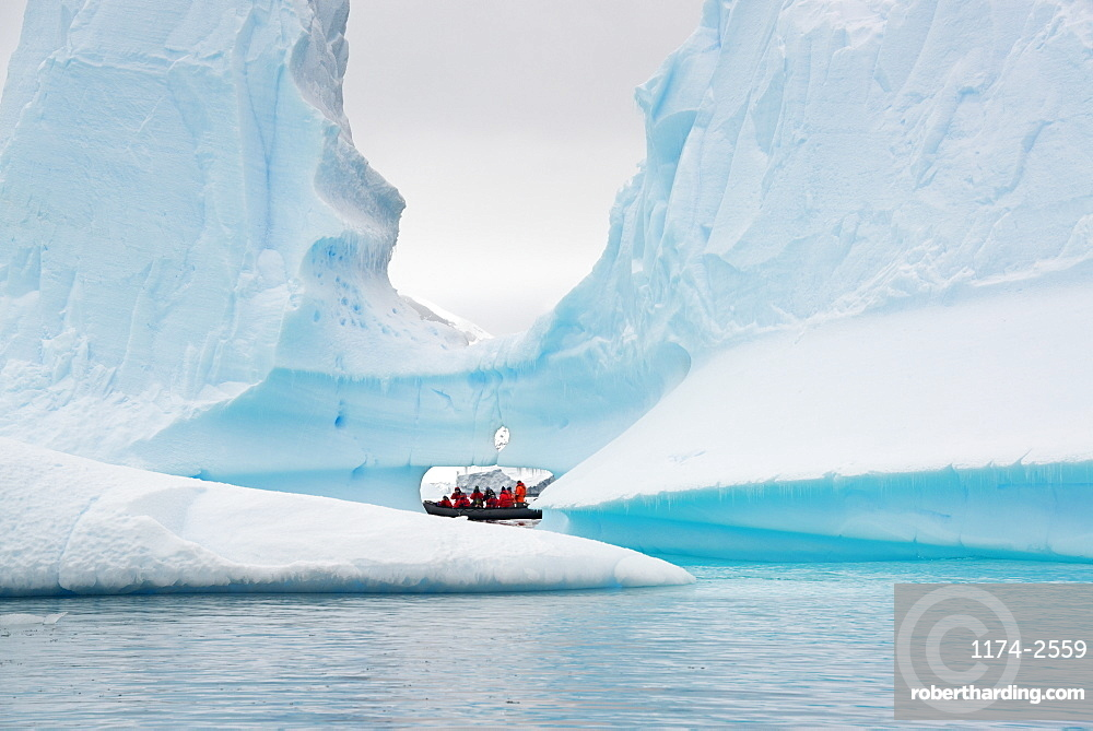 People in small inflatible zodiac rib boats passing towering sculpted icebergs on the calm water around small islands of the Antarctic Peninsula, Antarctic Peninsula, Antarctica