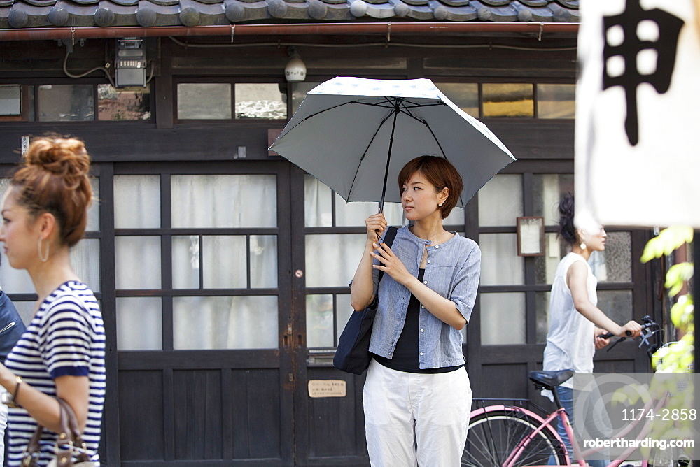 Woman standing outdoors, holding an umbrella, Osaka, Japan