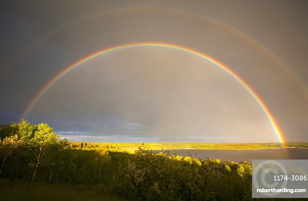 A double rainbow in the sky arching over the land, Rainbow, Saskatchewan, Canada