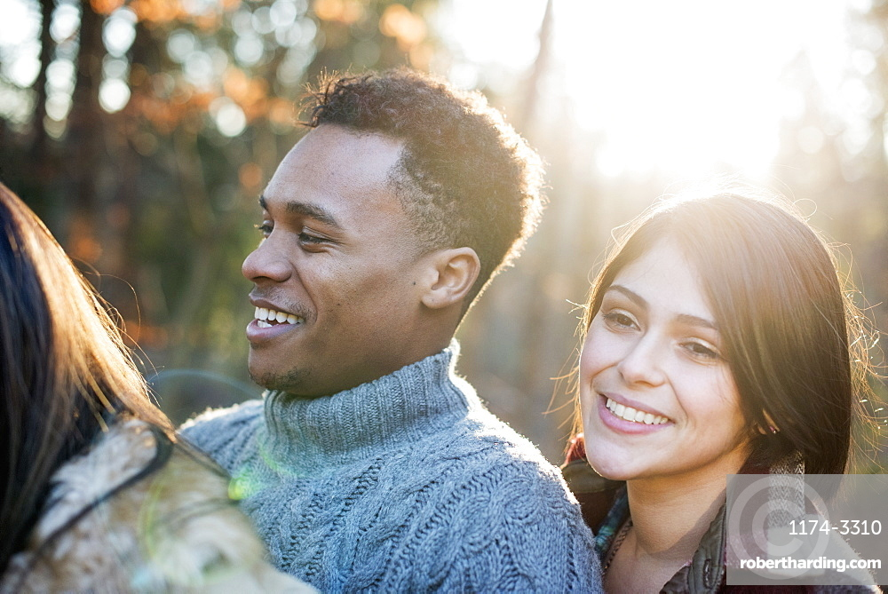 Smiling couple standing in a sunlit forest in autumn, Woodstock, New York State, USA