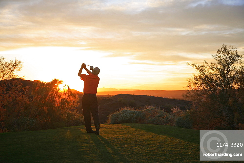 Golfer teeing off into the sunset on the golf course, Arizona, USA
