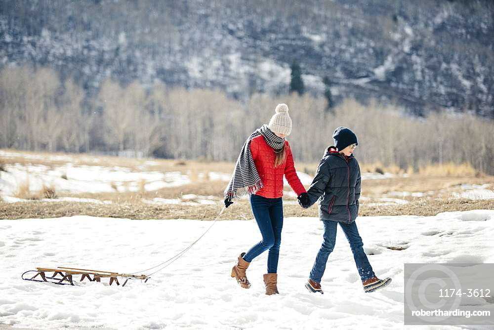 A brother and sister in the snow, one pulling a sledge, Mountains, Utah, USA