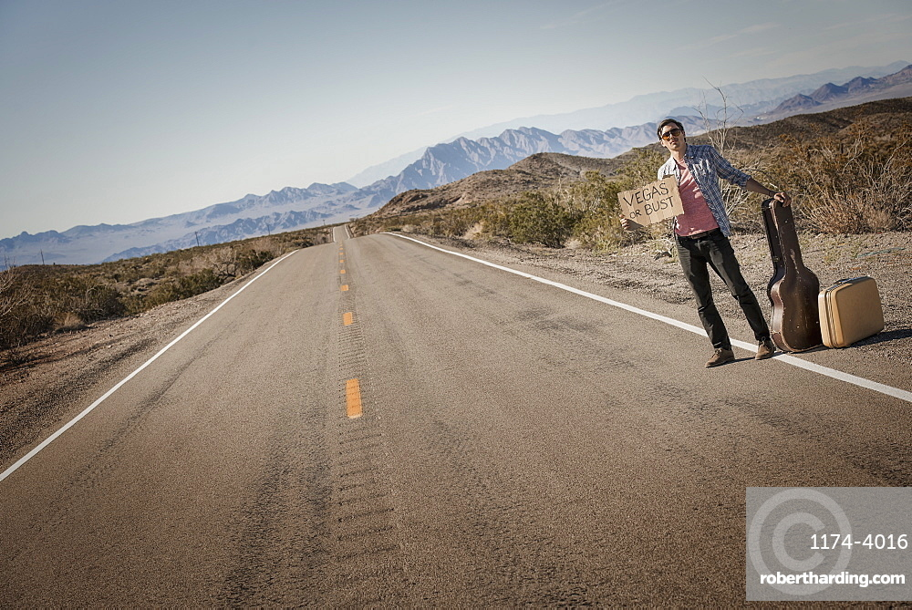 A man standing by the roadside, a hitchhiker with guitar and case, holding a sign saying Vegas or Bust, United States of America