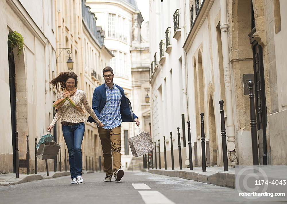 A couple walking along a narrow street in a historic city centre, with shopping bags, France